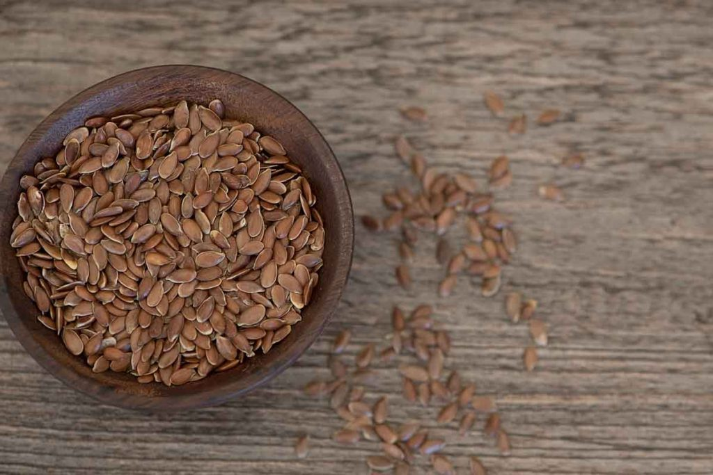 Flax seeds in a brown bowl on a wooden surface