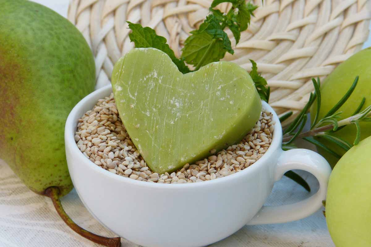 A green heart shaped shampoo bar in a white cup.