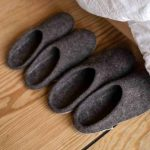 Two pairs of wool slippers by a bed